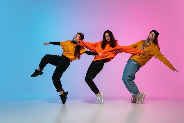 Девушки танцуют хип-хоп в стильной одежде на фоне градиентной студии в неоновом свете. Бесплатные Фотографии