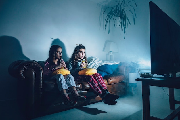 Girls in dark room watching movie Free Photo