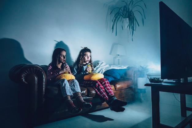 Girls in dark room watching movie Premium Photo