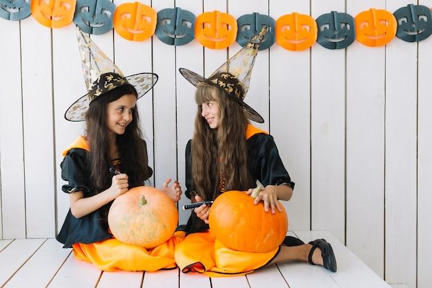 Girls decorating halloween pumpkins Free Photo