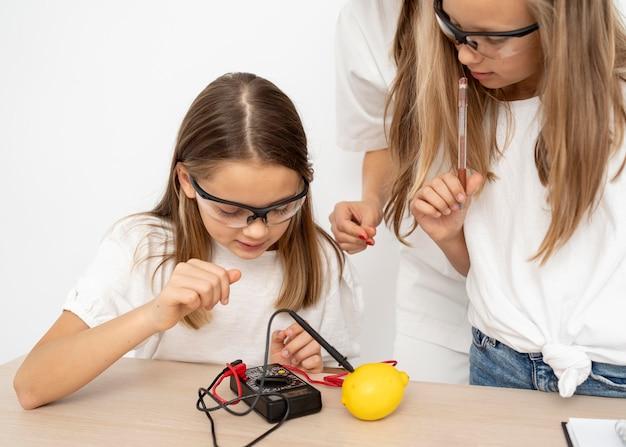 女教師とレモンで理科実験をしている女の子 無料写真
