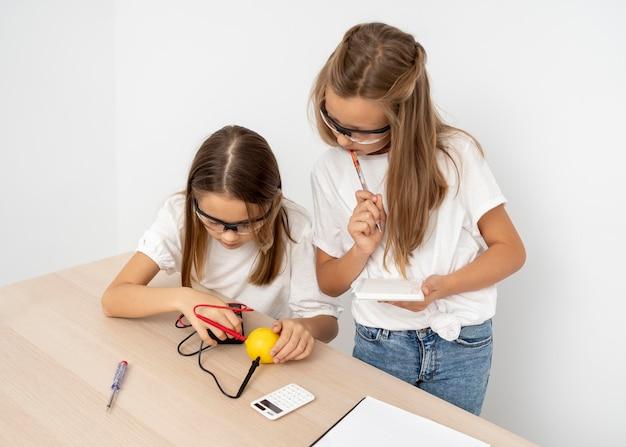 レモンと電気で科学実験をしている女の子 無料写真