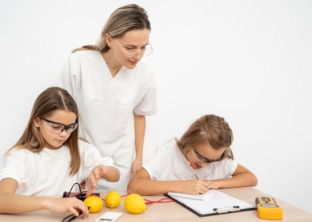 레몬과 전기로 과학 실험을하는 소녀들 무료 사진