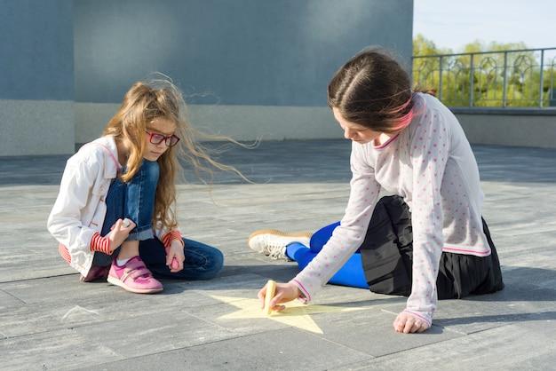 Girls draw on the asphalt colored crayons symbol Premium Photo