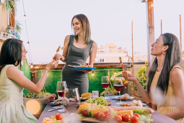 Girls eating appetizers at rooftop party Free Photo