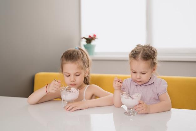 테이블에서 아이스크림을 먹는 여자 무료 사진