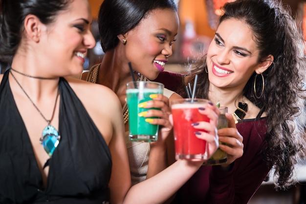Girls enjoying nightlife in a club, drinking cocktails Premium Photo