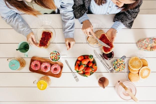Girls enjoying sweet colorful meal Free Photo