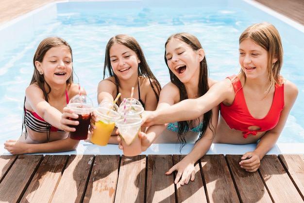Girls giving a toast in swimming pool Free Photo