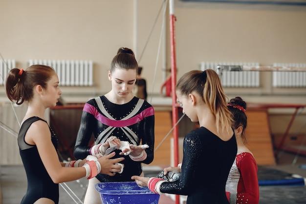 Ginnasta di ragazze in impugnature di ginnastica spalmando il gesso da palestra. bambini in una scuola di atletica leggera. Foto Gratuite