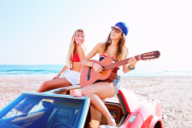 Girls having fun playing guitar on th beach in a car Premium Photo