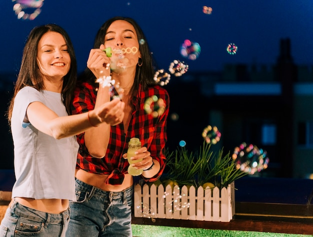 Girls having fun with soap bubbles and fireworks Free Photo