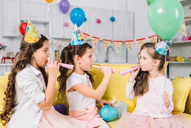 Girls holding balloons and blowing party horn during birthday Free Photo