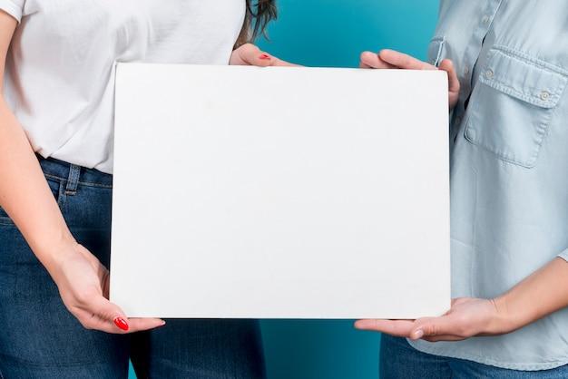 Girls holding blank board Free Photo