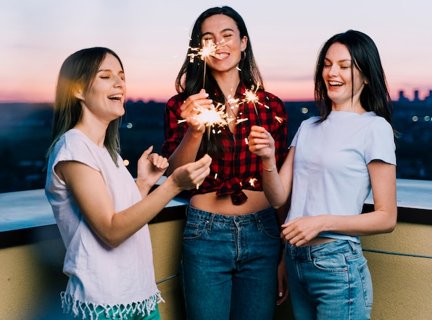 Girls holding fireworks on rooftop at dawn Free Photo
