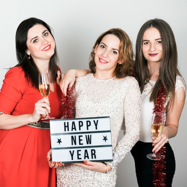 Girls holding happy new year sign Free Photo