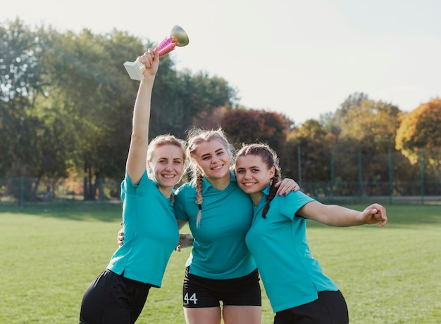 Girls holding a sport trophy and looking at photographer Free Photo