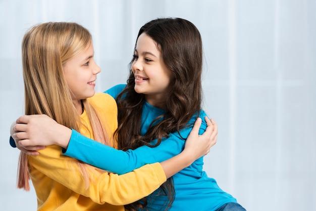 Девушки обнимаются и смотрят друг на друга Бесплатные Фотографии