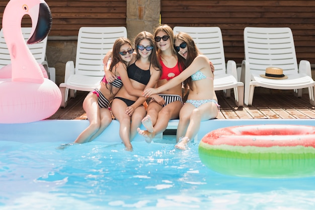 Girls hugging each other at swimming pool Free Photo