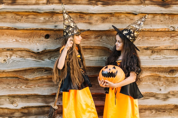 girls in halloween costumes with broom and pumpkin looking at each