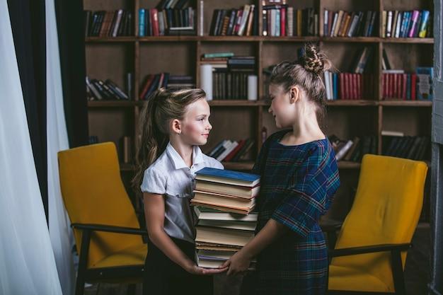 教育において厳格な方法で本を持っている図書館の女の子 Premium写真