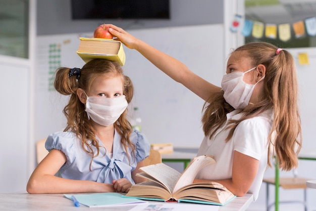 Girls playing in class while wearing medical masks Free Photo
