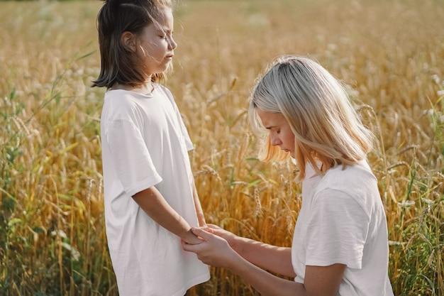 祈りと麦畑で手を繋いでいる女の子。神様が共に支え合うようにお祈りください。 Premium写真