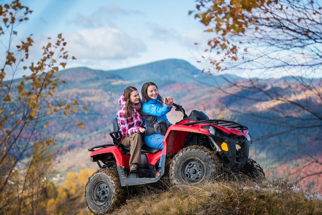 Girls on red quad bike at the hill makes selfie on the phone Premium Photo