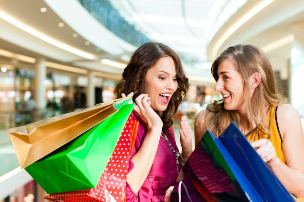 Girls shopping in mall looking in bags Premium Photo