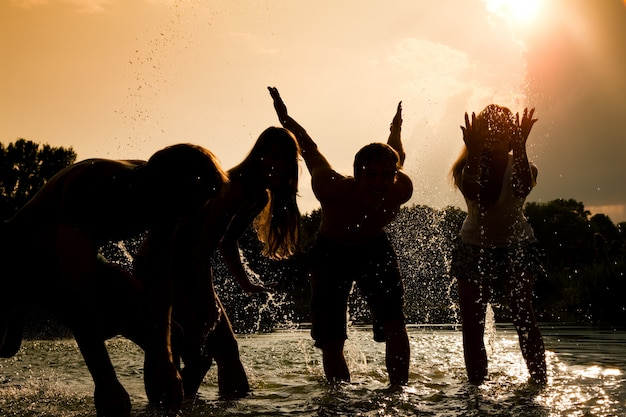 Girls' silhouettes playing in the water against the sun Premium Photo