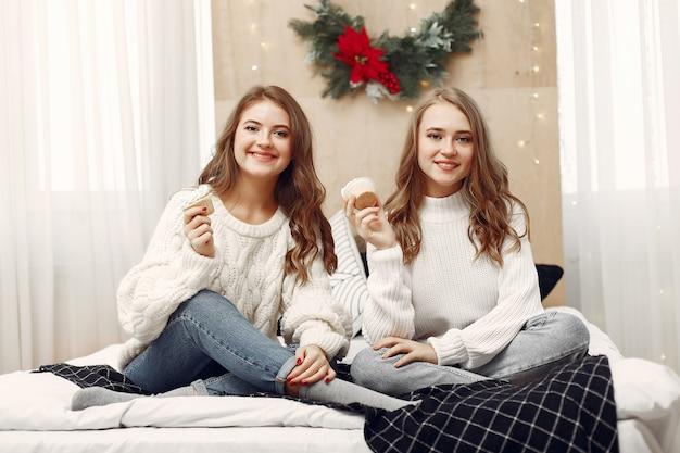 Ragazze sedute sul letto. donne con cupcakes. amici che si preparano per il natale. Foto Gratuite