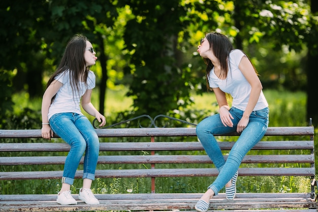 Girls sitting on bench making faces Photo