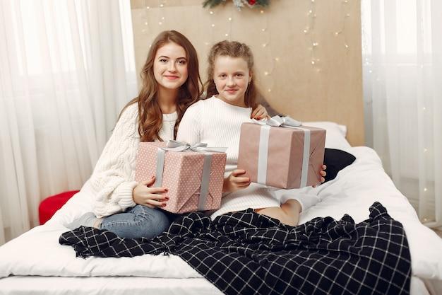 침대에 앉아있는 소녀들 선물을 가진 여성들 미녀들이 크리스마스를 준비하고 있습니다. 무료 사진