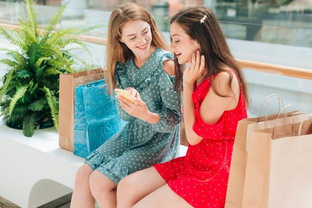 Girls sitting and talking at the mall Free Photo