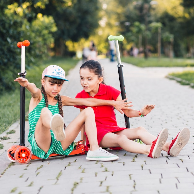 Girls sitting on their kick scooter enjoying in the park Free Photo