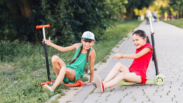 Girls sitting on their push scooter making fun in the park Free Photo