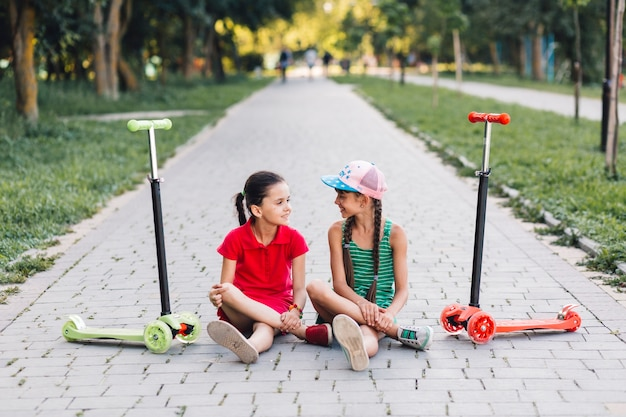 Girls sitting on walkway with their push scooters on walkway in the park Free Photo
