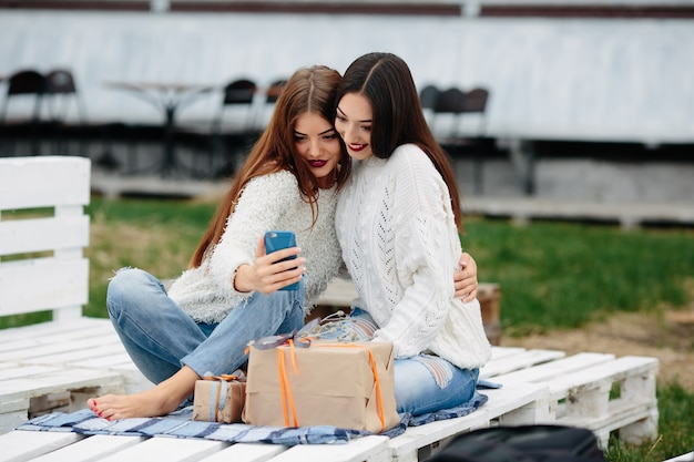 Girls sitting on a white wooden pallet with a gift looking at a mobile Free Photo