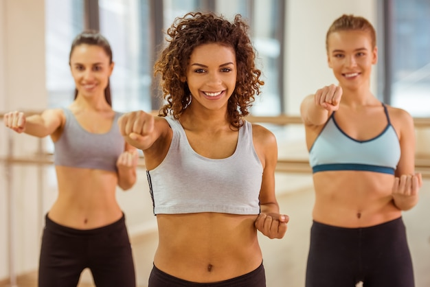 Girls smiling while working out and developing strength. Premium Photo