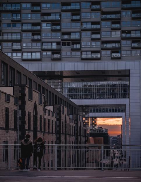 Девушки, стоящие возле перил, наблюдая закат Бесплатные Фотографии