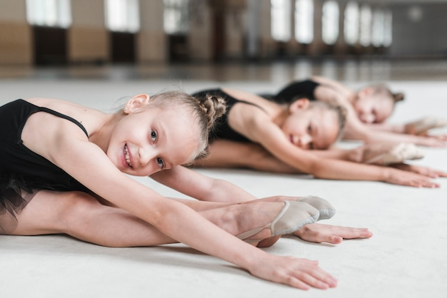 Girls stretching forward with her friends before dancing in studio Free Photo