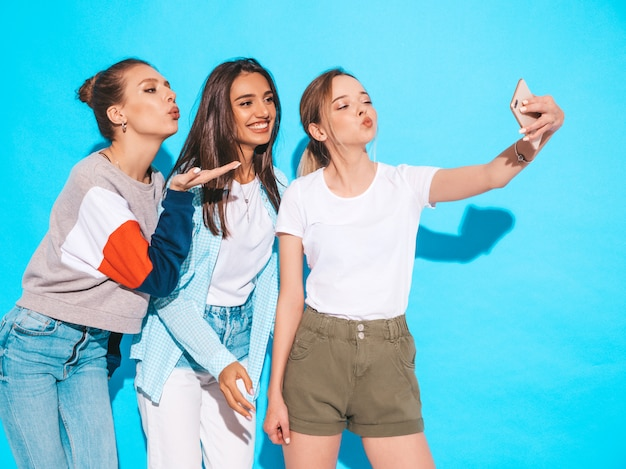 Girls taking selfie self portrait photos on smartphone.models posing near blue wall in studio.female making duck face on frontal camera Free Photo