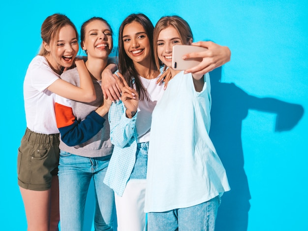 Girls taking selfie self portrait photos on smartphone.models posing near blue wall in studio,female showing positive face emotions Free Photo