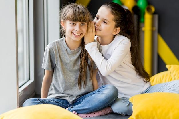 Girls telling a secret Free Photo