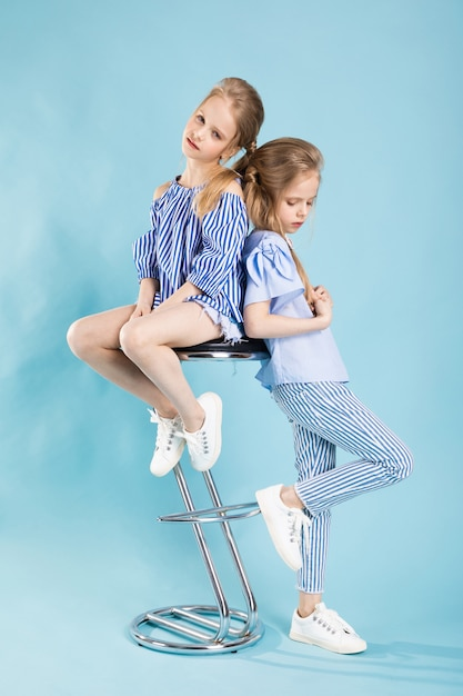 Girls twins in light blue clothes are posing near a bar stool on blue Premium Photo