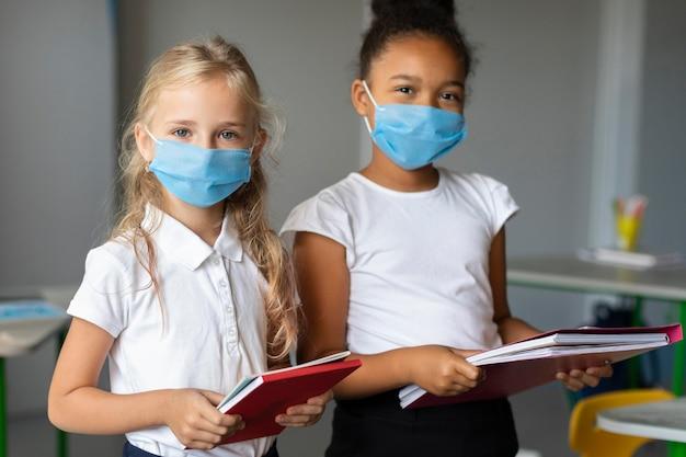 クラスで医療用マスクを着ている女の子 無料写真