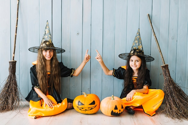 Girls in witch costumes with brooms sitting by fence Free Photo