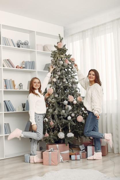 크리스마스 장난감을 가진 여자. 집에서 여자. 자매들은 휴가를 준비하고 있습니다. 무료 사진
