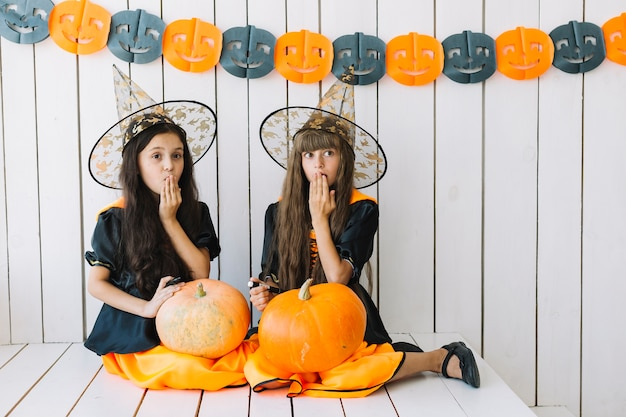 Girls with halloween pumpkins closing mouth with hand Free Photo