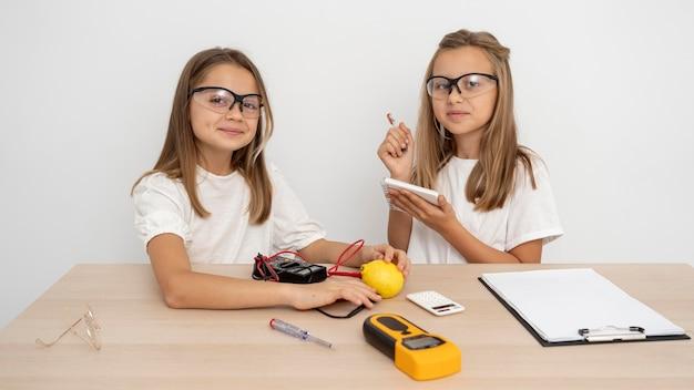 Ragazze con occhiali di sicurezza che fanno esperimenti scientifici Foto Gratuite
